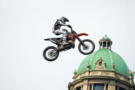 supercross: Motocross rider performing extreme jump next to cupola of old stylish building