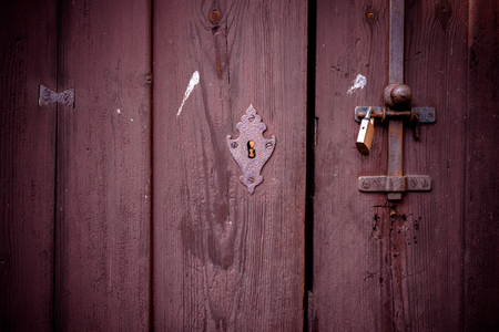 iron gate: Old wooden door of the antique house closed with chains and padlock. Stock Photo