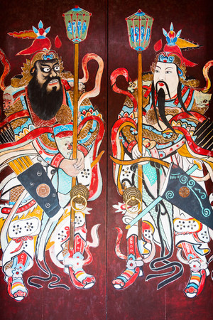 guardians: Guardians painted on an old door in Hoi An, Vietnam Stock Photo
