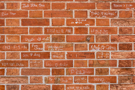 bark carving: Old red brick wall with lovers signs Stock Photo