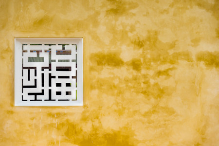 Zeer oud Chinees venster op gele muur. Hue, Vietnam.