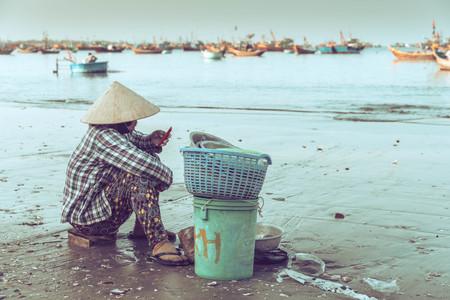ne: Woman sitting on the beach, Mui Ne, Vietnam - retro color