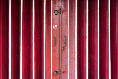 Closed red old shuttered roll metal door with lock