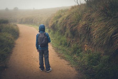 Jonge jongen met een rugzak loopt op een weg Stockfoto