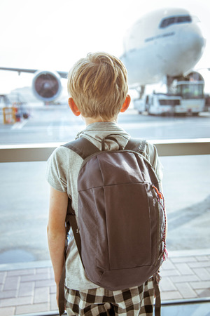 Jongen kijkt naar vliegtuigen op de luchthaven Stockfoto