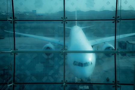 Vliegtuig achter glas op de luchthaven Stockfoto