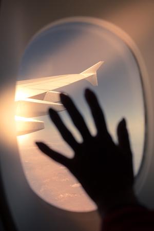 Silhouet van vrouw overhandigen het vliegtuigvenster met licht effect.