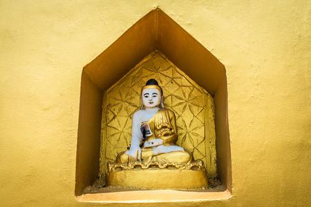 Een klein boeddhistisch altaar met boeddhabeelden.