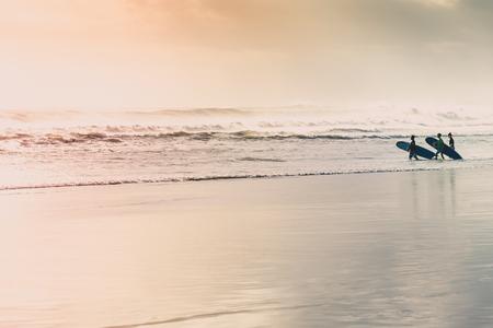 Surfers die op het strand bij zonsondergang lopen.