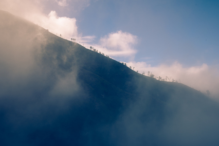 Foggy over hill in the morning with blue sky.