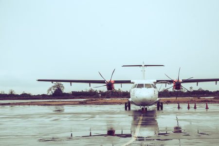 Propeller plane parking at the airport under rain. Stockfoto