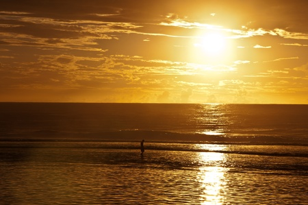 Lone person in the walking in the water of the lagoon off the beach as the sun goes down in a golden ball in Rarotonga, Cook Islands
