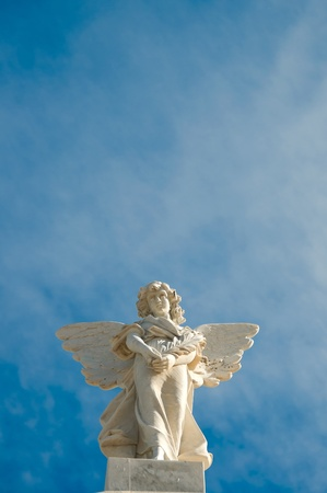 Concrete angel on a pedestal against the blue sky