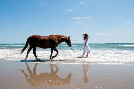 Horse and girl running through the sea