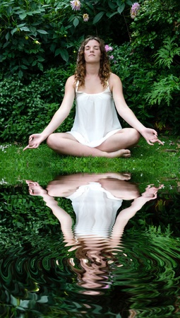 Woman meditating in front of reflection pool Stock Photo