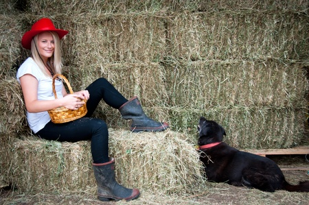 gumboots: Country girl sitting on hay bale with basket with her faithfull black farm dog Stock Photo