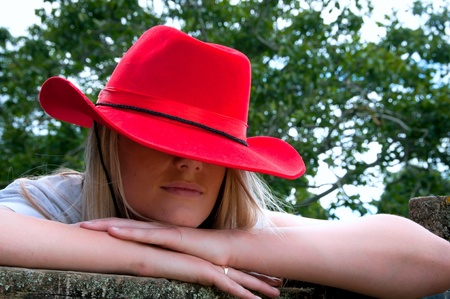Blonde girl leaning on fence with red stetson style hat on at a farm Stock Photo