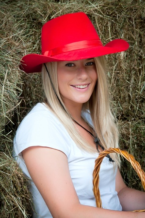 stetson: Country girl sitting in the haybarn with a red stetson style hat