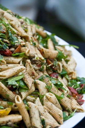food buffet: Pasta salad with sun dried tomatoes and spinach Stock Photo