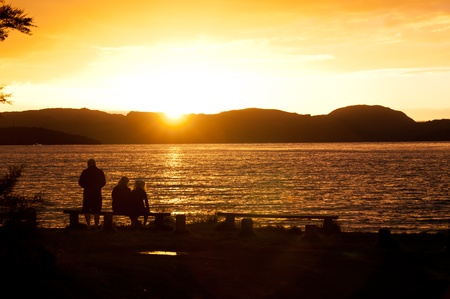 Family in silhouette watching sunset over lake Stock Photo