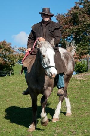 stockman: Farmer riding horse Stock Photo