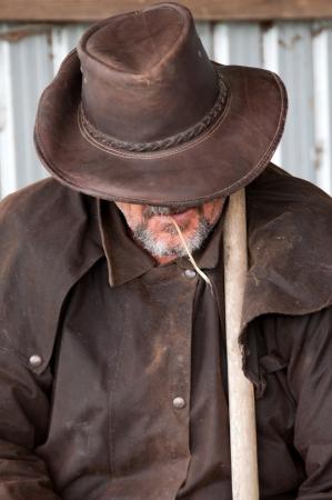 Farmer in barn chewing hay