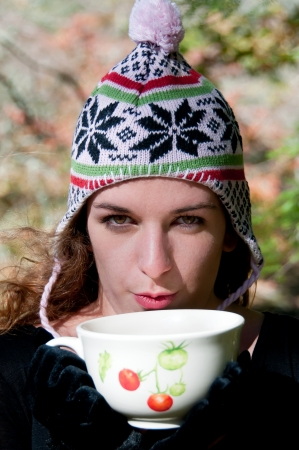 Woman with hot drink outdoors in autumn Stock Photo