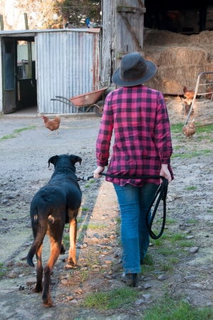 Farm girl and dog coing to feed the hens photo