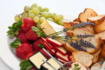 Plate of strawberries, cheeses and grapes Stock Photo