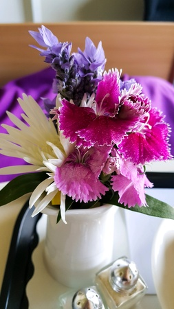 Little vase of flowers on hospital bed tray Stock Photo