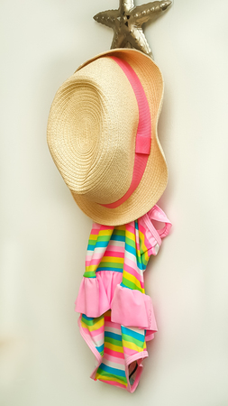 sunhat: Swimsuit and beach hat hanging on a hook
