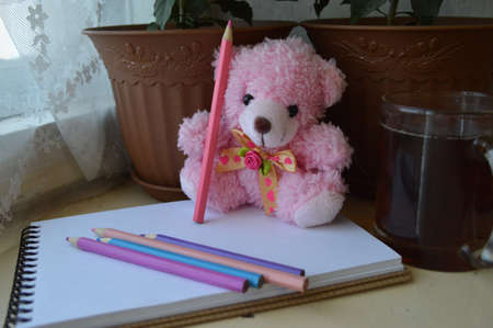 Cute pink teddy bear with a pencil in a paw and a cup of tea near the window