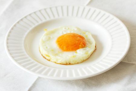 fried egg on white plate - white background