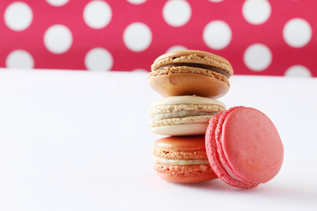 Sweet and colourful french macaroons on polka dot background  photo