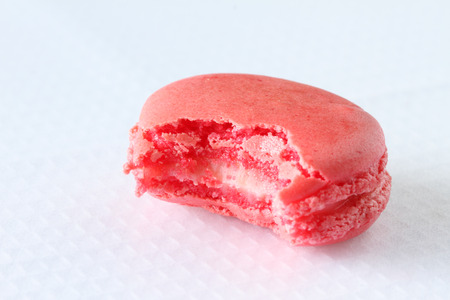 bitten french macaroon on white background photo