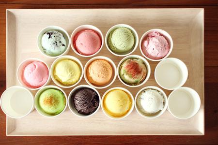 comiendo helado: bolas de helado dulces y coloridas en la placa de madera Foto de archivo