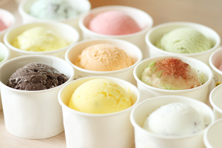 sweet and colorful ice cream scoops in white cups photo