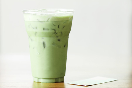 glass of green tea latte on wooden background photo