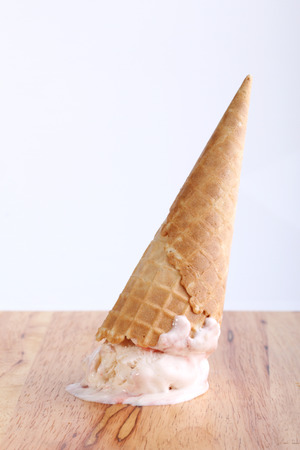 ice cream cone dropped upside down on wooden background Stock Photo