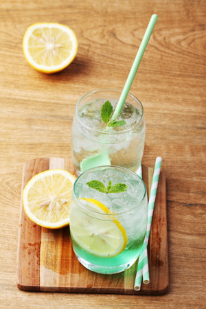 cold soft drink from apple syrup and mint with green spoon on wooden board photo