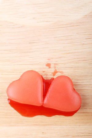 crimson colour: two red heart-shaped ice from raspberry syrup on wooden background Stock Photo