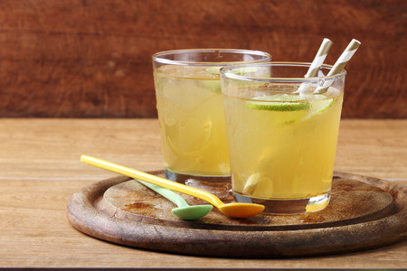 fruit in water: cold gold soft drink from lime and honey with gold straw on wooden board