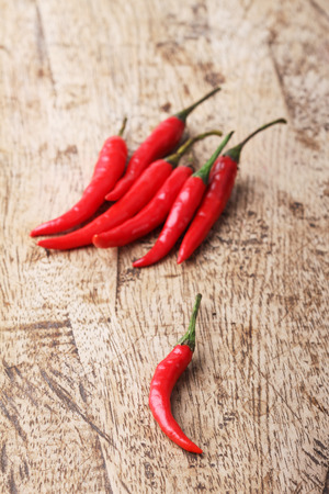capsaicin: Red Hot Chili Peppers on wooden background Stock Photo