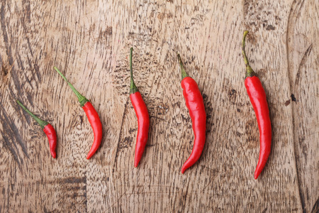 grow up: Red Hot Chili Peppers grow up on wooden background Stock Photo