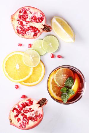pomegranat: glass of pomegranate drink with fresh  citrus fruits on white background Stock Photo