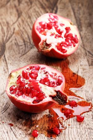 pomegranat: pomegranate, red juicy pomegranates on wooden background Stock Photo