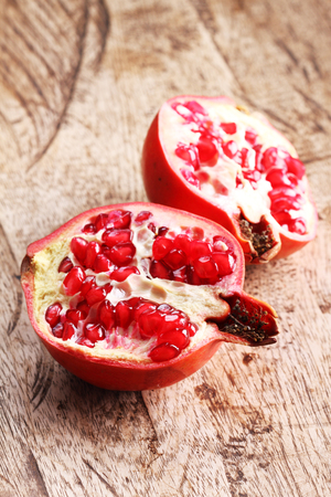 pommegranate: pommegranate, red juicy pommegranates on wooden background Stock Photo