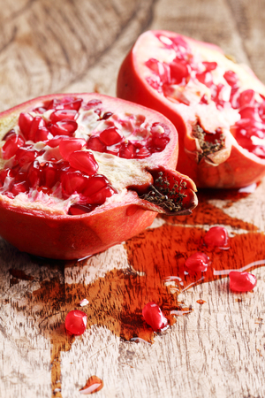 pommegranate: pomegranate, red juicy pomegranates on wooden background Stock Photo