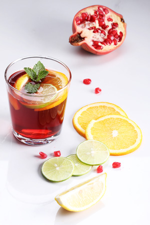 pomegranat: glass of pomegranate drink with fresh citrus fruits on white background