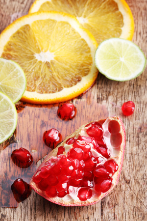 pommegranate: red juicy pomegranate with citrus fruits on wooden background
